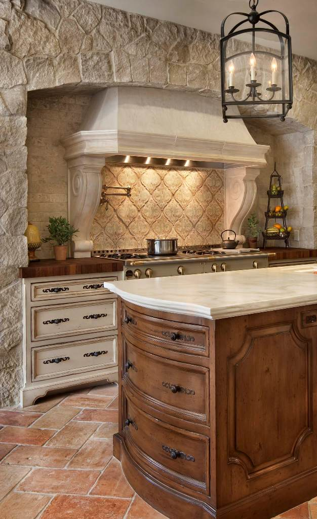 Rustic stone-sided modern fireplace and countertops in Tuscan kitchen