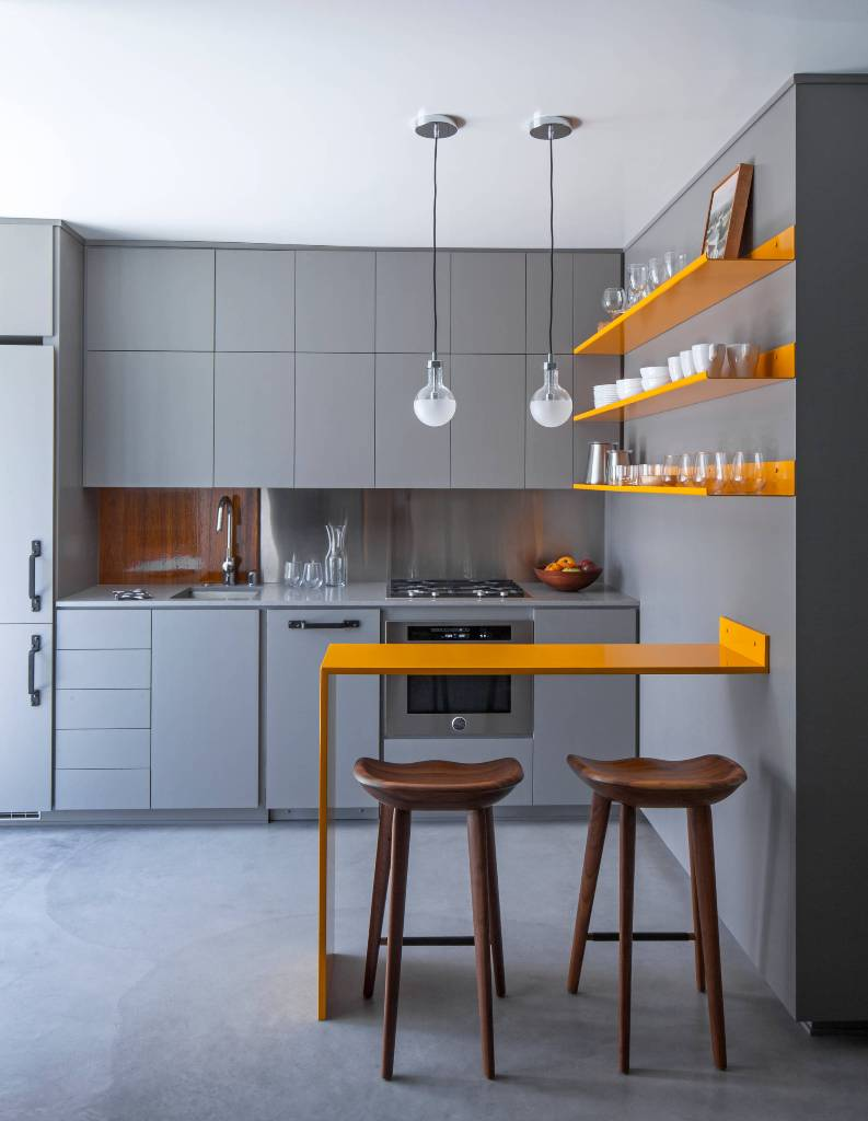 Small modern kitchen with concrete floor with a wall