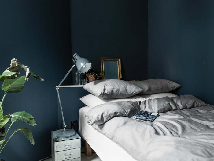 Light gray linen bedding dark blue bedroom wall
