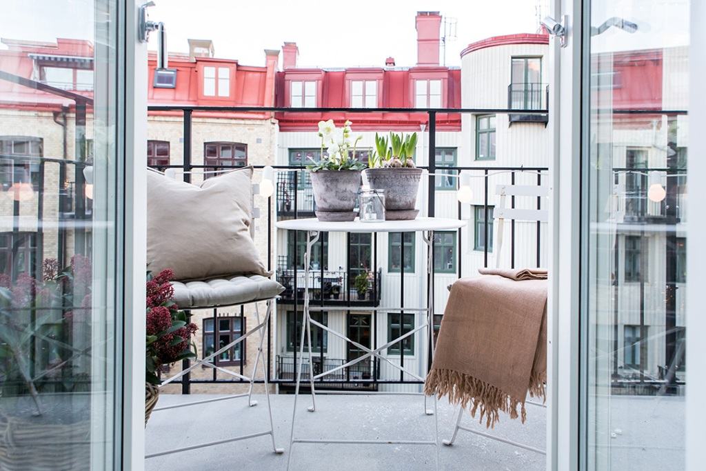 cute balcony with flower pot and two chairs