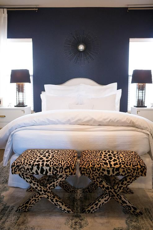 White and navy blue bedroom features an accent wall painted navy .