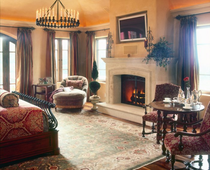 cozy-bedroom-with-a-fireplace-club-chairs-and-antique-table-and .