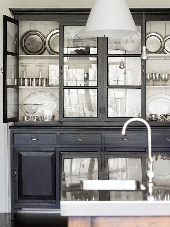 Painted black cabinetry with glass fronts backed with wide white .