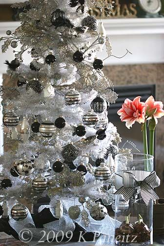 White flocked Christmas tree with black and silver ornaments .