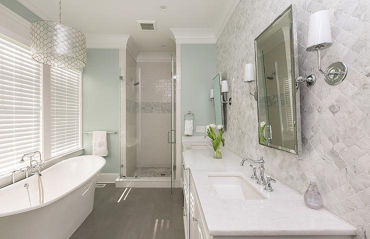 White and Blue Spa Like Bathroom with Gray Wood lIke Floor Tiles .