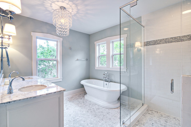 Spa-like master bath with glass chandelier and pedestal tub .