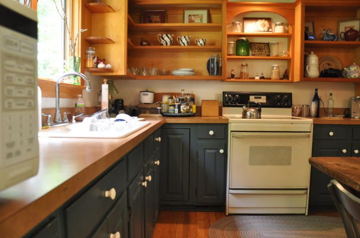 Two tone kitchen - dark blue base cabinets and natural wood uppers .