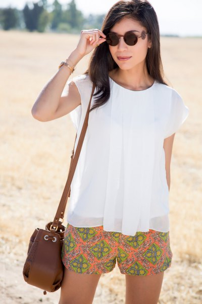 white chiffon top with cap sleeves and orange, flowing shorts
