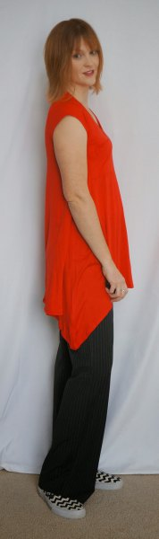 asymmetrical sleeveless tunic with black pants with wide legs