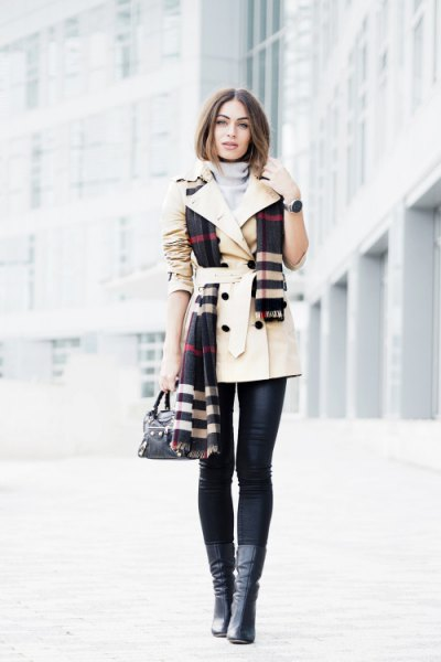 beige trench coat with belt and black and white checked scarf