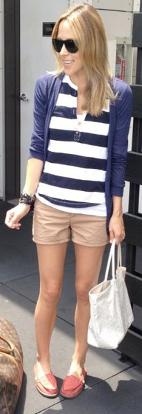 beige khaki shorts with a dark blue and white striped polo shirt