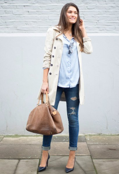 beige long coat with light blue shirt and torn skinny jeans