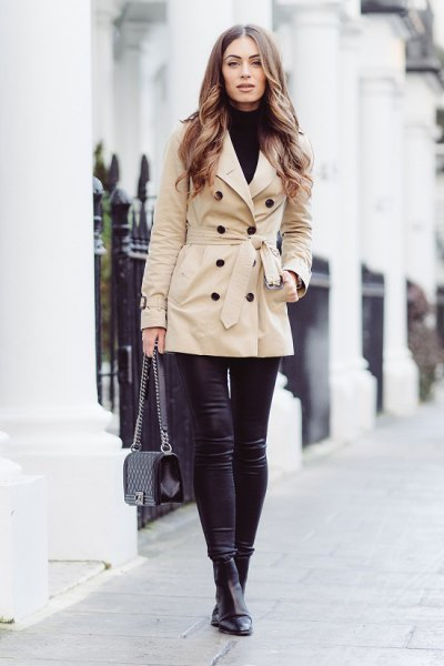 beige wrap coat with black turtleneck and leather gaiters