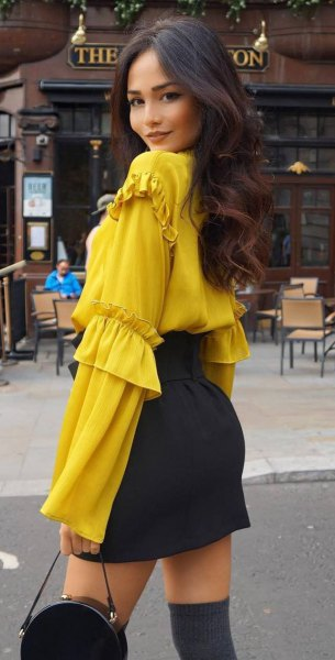 Mustard blouse with bell sleeves and black mini skirt