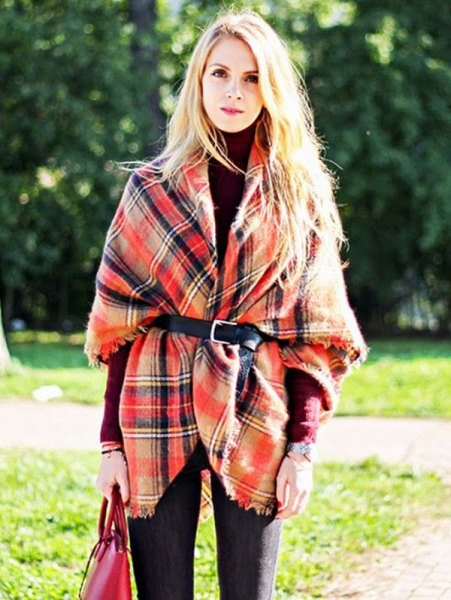 Plaid wrap-around sweater with belt and dark blue jeans