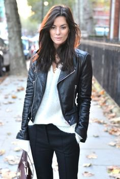 Biker jacket with a white knitted V-neck sweater and black chinos