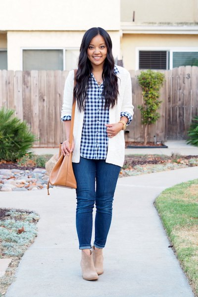 black and white checked shirt with white cardigan and blue skinny jeans