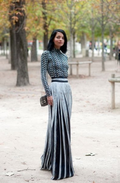 black and white patterned mock-neck blouse with a silver pleated maxi skirt