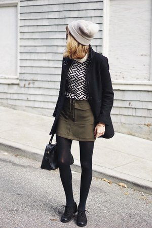 black and white patterned sweater with a green mini waist skirt