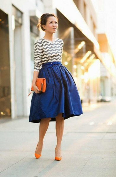 black and white patterned top with a royal blue flared skirt and orange heels