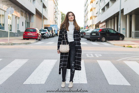 black and white checked long wool coat with white sweater with a mock neck