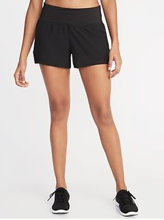 black and white sneakers with shortened sports tank top and mini running shorts