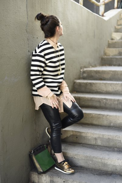 black-and-white striped long-sleeved sweater with leather pants and bronze-colored metallic sneakers