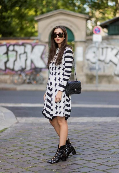 black and white striped mini dress with pointed toe boots made of leather