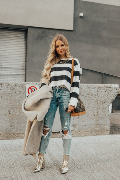 black and white striped sweater with ripped jeans and gold boots