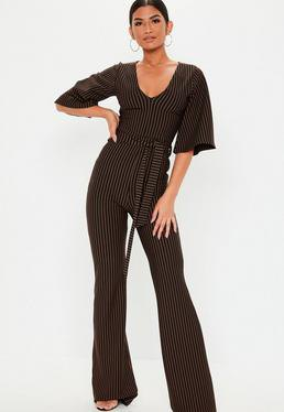 Black and white jumpsuit with vertical stripe and V-neckline and wide sleeves