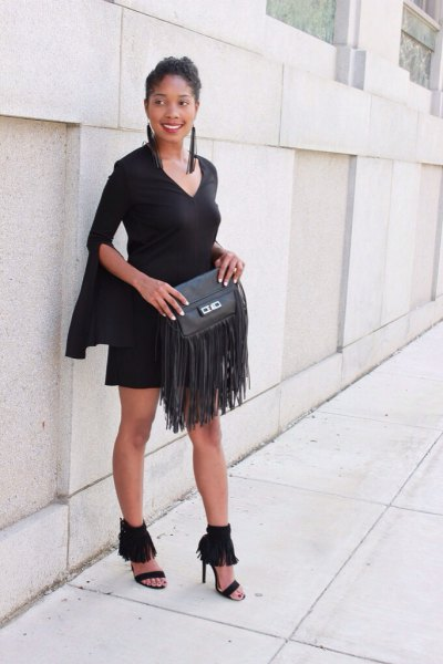 black shift dress with bell sleeves and wallet with leather fringes