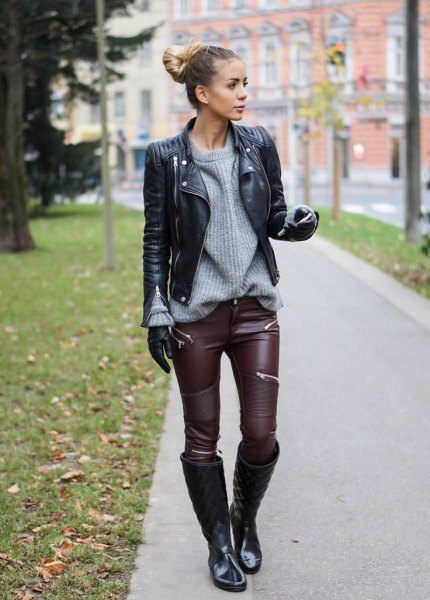 black biker jacket with gray, ribbed sweater and leather gaiters