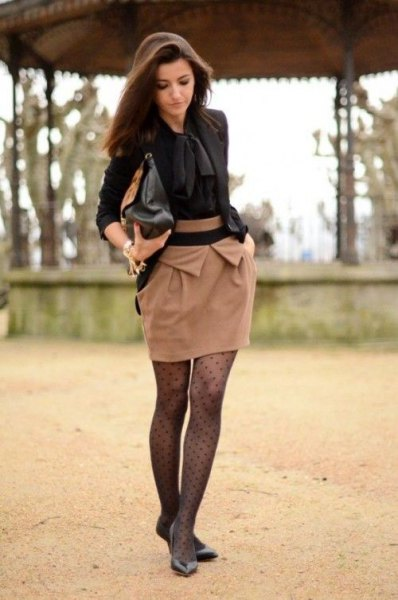 black blouse with a blushing pink mini skirt and tights with a polka dot pattern