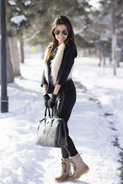 black blouse with faux fur vest and white snowshoes