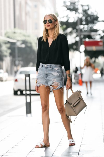black blouse with torn shorts and white slide sandals