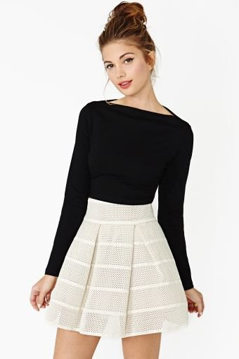 black long-sleeved top with boat neckline and light pink minirater skirt