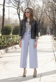 black bomber jacket with black and white striped sweater and blue pants with wide legs