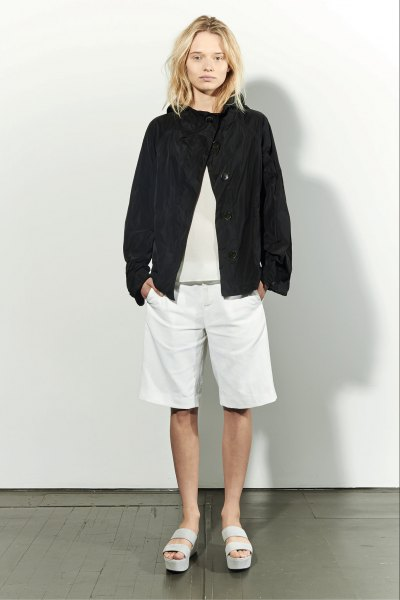 black bomber jacket with light pink sweater and white long shorts