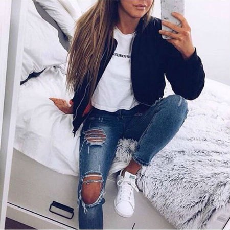 black bomber jacket with white graphic t-shirt and really torn blue jeans