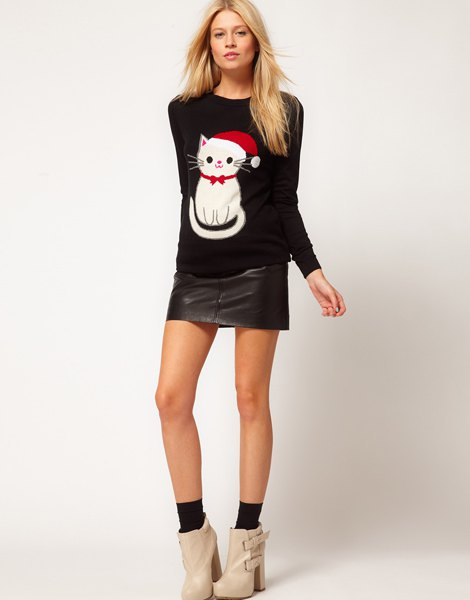 black sweater with cartoon cat print and mini leather skirt