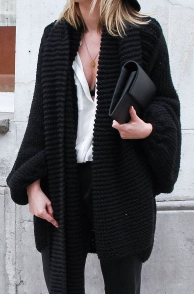 black, coarsely knitted cardigan with white blouse and leather handbag