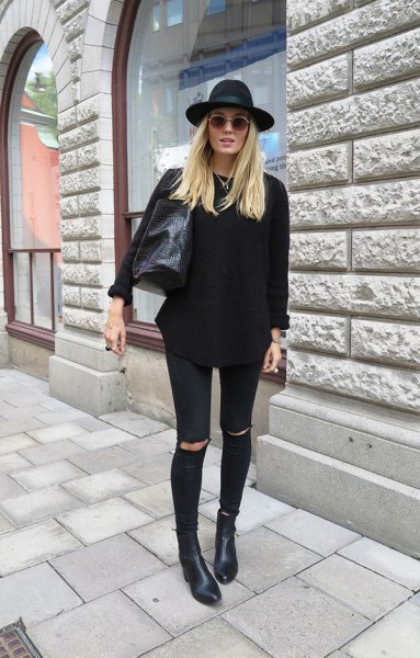 black, chunky sweater with torn jeans and a felt hat