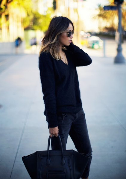 black, coarsely knitted sweater with V-neck and dark, narrow-cut jeans