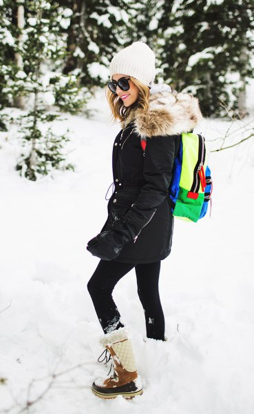 black coat with leggings and white and brown mid-calf snowshoes