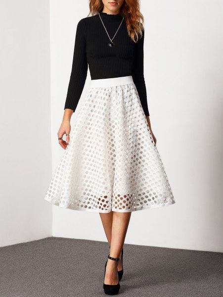 black sweater with round neckline and white, semi-transparent midi skirt