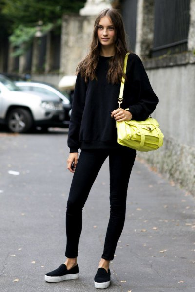 black knitted sweater with round neckline and lemon yellow leather shoulder bag