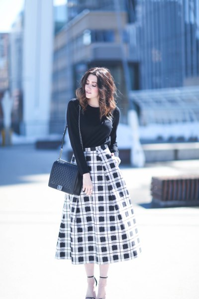 black sweater with round neckline and high-waisted, checked midi skirt
