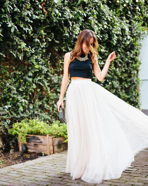 black, short, sleeveless top with white, high-waisted maxi pleated skirt