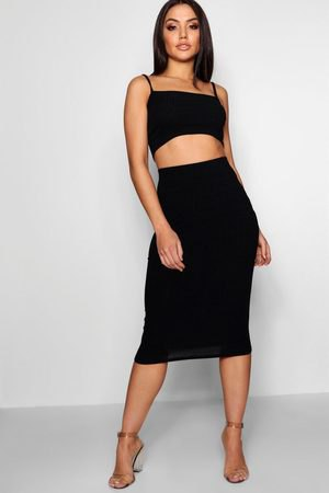 black, short-cut vest top with a square neckline and a high-waisted, figure-hugging midi skirt