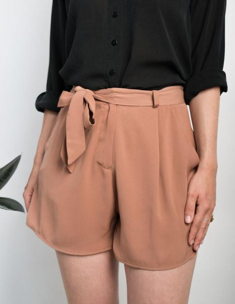 black shirt with cufflinks and blushing pink mini-shorts